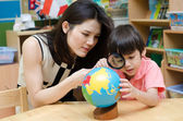 Portrait student looking at globe while listening to teacher — Stockfoto