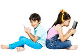 Little boy and girl playing phone and tablet on white background — Stock Photo
