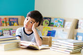 Little boy reading book thinking face — Stock Photo