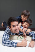 Father and sons laying together happy face — Stock Photo