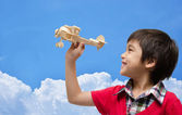 Little boy playing airplane wood toy with blue sky — Stock Photo