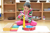 Little girl hand building tower made of montessori educational m — Stock Photo