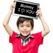Little boy holding tablet computer word mommy I love you — Stock Photo #48413939