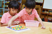 Little boys study color of pin made of montessori educational ma — Stock Photo