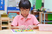 Little boy study color of pin made of montessori educational mat — Stock Photo