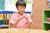 Little boy with Montessori material colored beads — Stock Photo