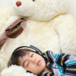 Little boy listening the music with headset while sleeping — Stock Photo #50275321