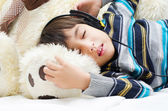 Little boy listening the music with headset while sleeping — Stockfoto