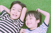 Little sibling boy lay down on grass vitage style — Stock Photo