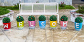 Flower pots arrange with welcome letter — Stock Photo