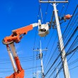 Electrician repairing power line and blue sky in background — Stock Photo #31983329