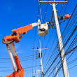Electrician repairing power line and blue sky in background — Stock Photo
