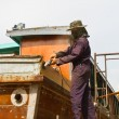 Carpenter is repairing boat in dry dockyard — Stock Photo