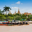 Long-tailed boat in Chao Phraya River and the Grand Palace in background — Stock Photo