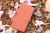 Smartphone leather case cover on dried leafs and flower — Photo