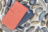 Smartphone leather case cover on gravel texture floor — Photo
