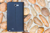 Smartphone leather case cover on gravel texture floor — Stok fotoğraf