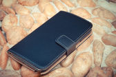 Smartphone leather case cover on gravel texture floor in vintage picture style — Photo