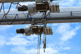 Heavy industry crane motor and hook on blue sky background — 图库照片