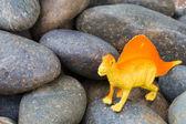 Plastic dinosaur on pebble stone — Stock Photo