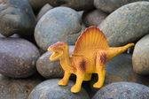 Plastic dinosaur on pebble stone background — Foto de Stock