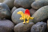 Plastic dinosaur on pebble stone background — Stock Photo