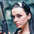 Young woman with gun wearing glasses — Stock Photo
