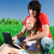 Long-haired girl with notebook and with boy on grass — Stock Photo #48138711