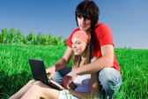 Long-haired girl with notebook and with boy on grass — Stock Photo