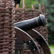 Old cannon standing between wicker ramparts — Stockfoto