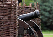 Old cannon standing between wicker ramparts — Stock Photo