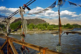 Tibetan praying flags adorning the bridge over the Indus river with Tibetan monastery and Himalayas in the background — Stock Photo