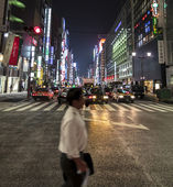 Blurred figure of a salariman as he crosses the street in Ginza — Stock Photo