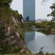 The moat of Osaka Castle with modern buildings in the distance — Stock Photo