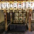 Stock Photo: Fragment of shinto shrine with purification ladles, sake offerings and white lanterns