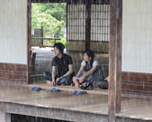 A young Japanese couple look at the rain from the temple buildi — Stock Photo