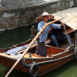 A boatwoman transports tuorists in her traditional wooden boat i — Stock Photo