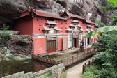 Temple building leaning against a vertical rock in Qiyun Taoist — Stock Photo
