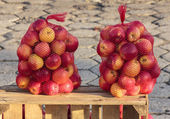 Two bags full of delicious red apples standing on a wooden chest — Stock Photo