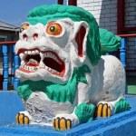 Colorful statue of shishi lion guards entrance to lamaist temple — Stock Photo #37972715