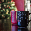 Stock Photo: Two mugs red and black decorated with chinese calligraphy blurre