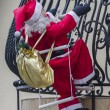 Big figurine of Santa Claus attached to a house's balcony so as — Stock Photo