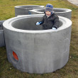 Baby boy standing inside big concrete pipe — Photo #38244013