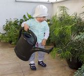 Baby boy waters flowers on a terrace with a big watering can — Stock Photo