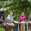 Foto Stock: Black musicifrom Africdemostrates how to play drums to
