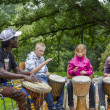 Stockfoto: Black musicifrom Africdemostrates how to play drums to