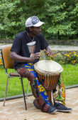 : Black musician from Africa demostrates how to play the drums — Zdjęcie stockowe
