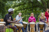 Black musician from Africa demostrates how to play the drums to — Zdjęcie stockowe
