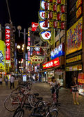 Brightly lit street with numerous billboards and neons in Dotomb — Stock Photo