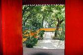 Rote tür offenbart einen schönen tempel-hof in putuo shan, c — Stockfoto